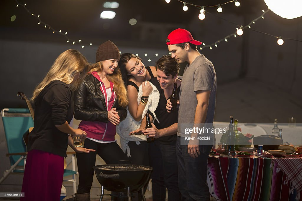 Young adult friends keeping warm at rooftop party : Stock Photo
