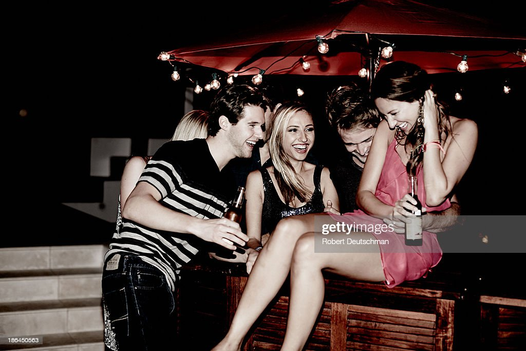 Young adult friends laughing together at night.