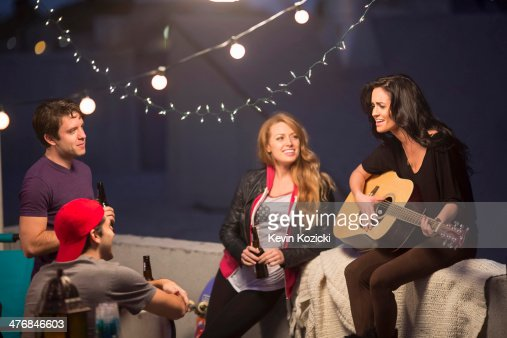 Young adult friends listening to guitar at party : Stock Photo