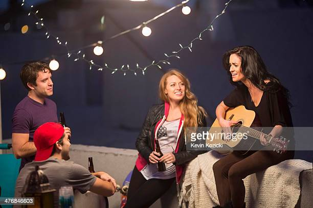 Young adult friends listening to guitar at party