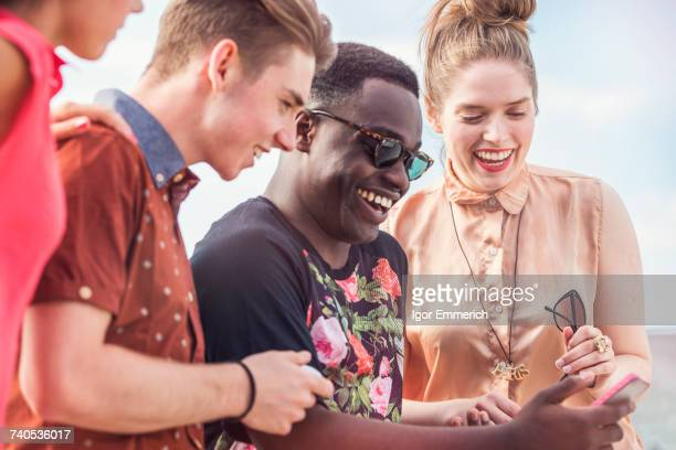 Young adult friends looking at smartphone