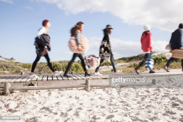 Young adult friends on the move on beach boardwalk, Western Cape, South Africa