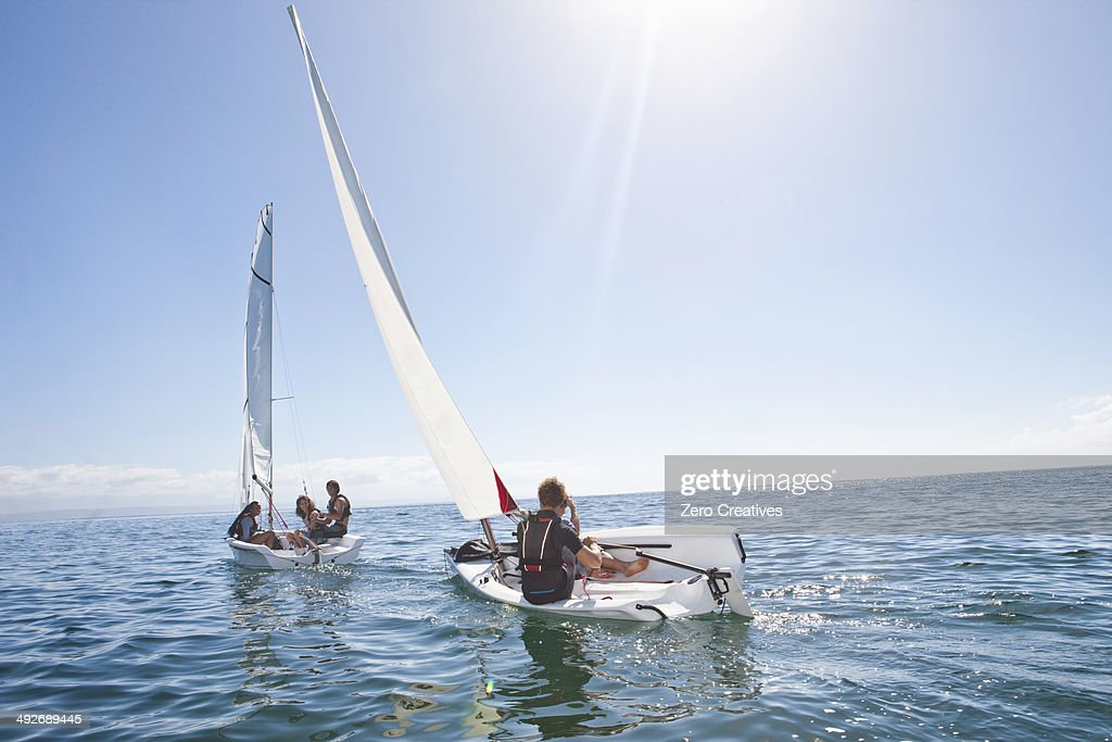 Young adult friends racing each other in sailboats