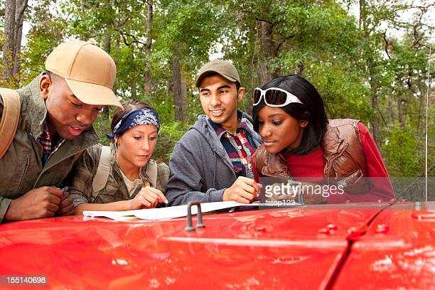Jeune adulte amis de lecture de carte en jeep sur la capuche.