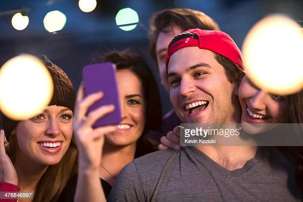 Young adult friends taking selfie at party