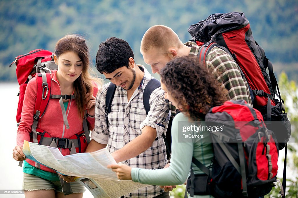Young adult group of friends reading a trailmap