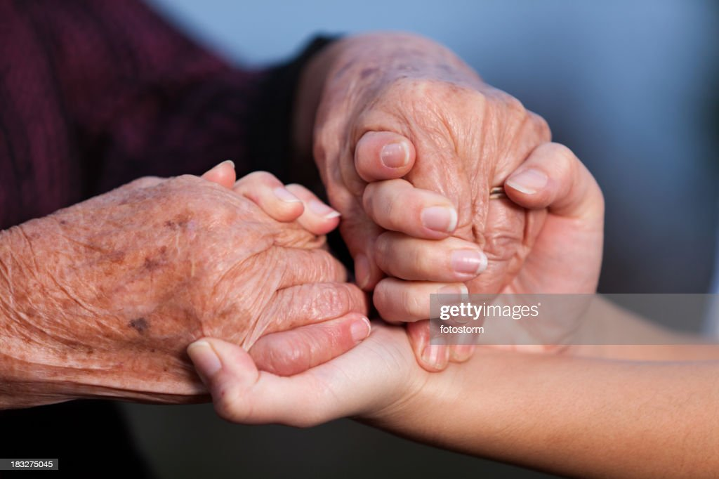 'Young adult helping senior women, holding hands'