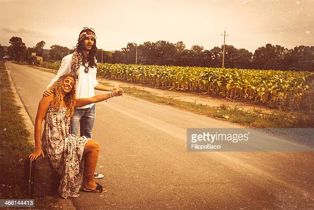 Young adult hippie couple hitchhiking