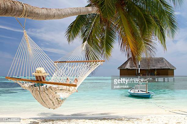 Young adult in hammock contemplating the sea view