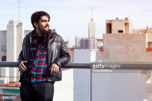 Young adult leaning on rooftop balcony