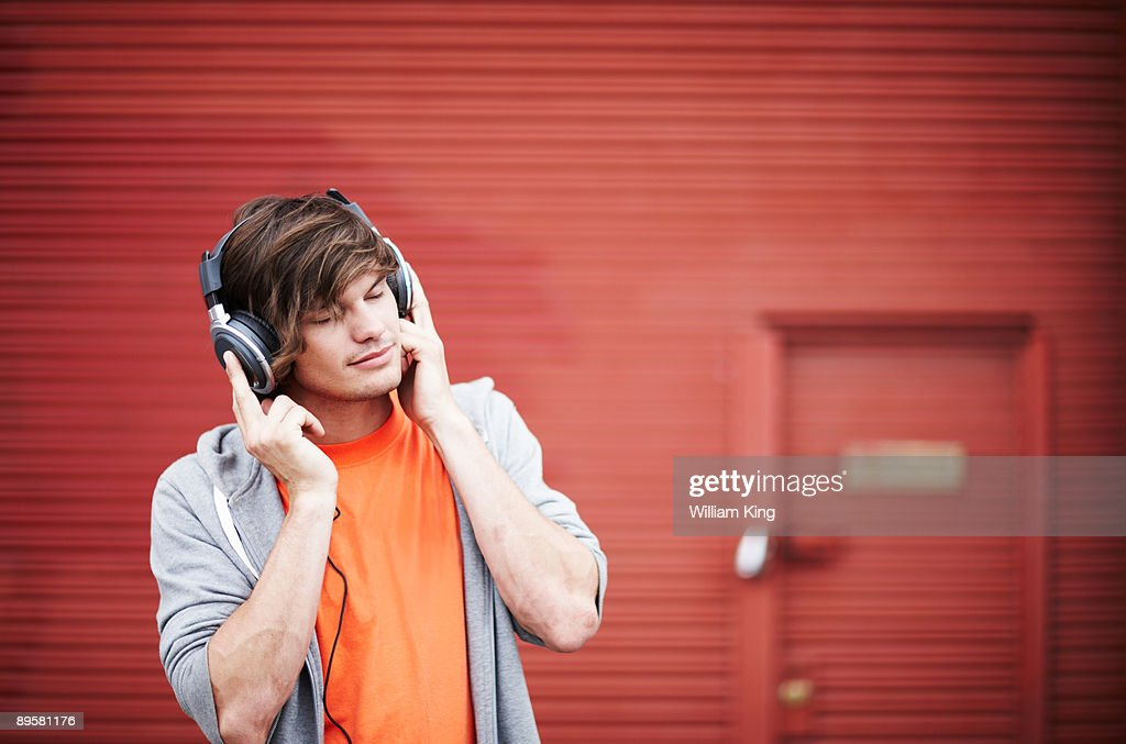young adult listening to music on headphones : Stock Photo