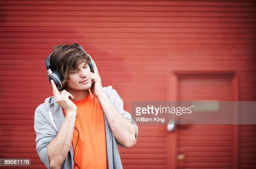young adult listening to music on headphones : ストックフォト