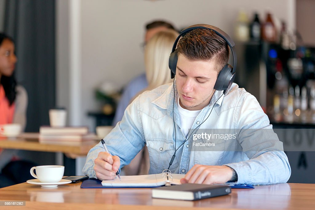 Young adult male listening to music and doing homework