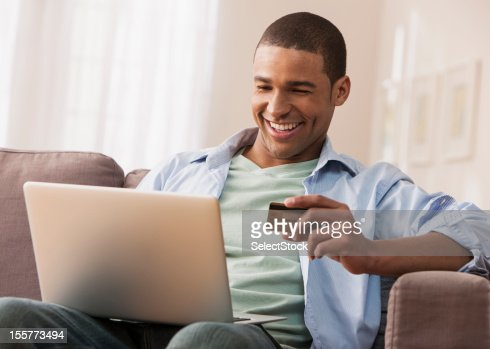 Young adult male making online purchase : Stock Photo