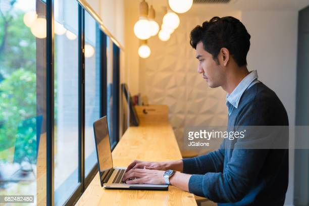 Young adult male sat using his laptop in a modern office