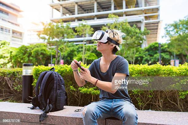 Young adult male using VR technology outside