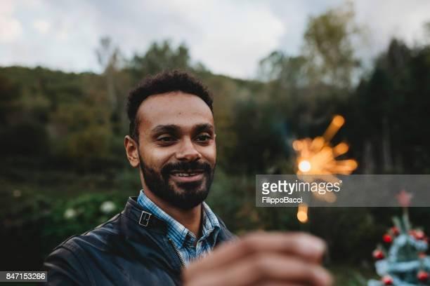 Young adult man holding a sparkler firework