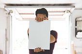 Young Adult Man Holding White Paper with geometric perspective in background