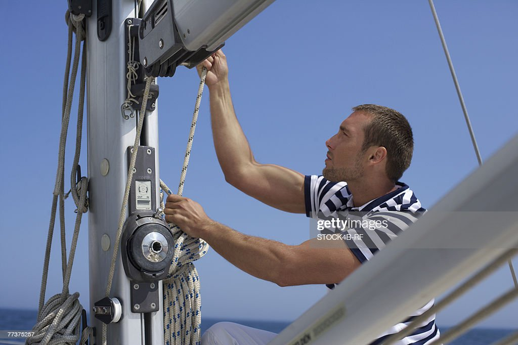 Young adult man is pulling a rope on a sailing boat