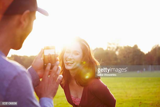 young adult man is taking a photo of his girlfriend with his mobile phone