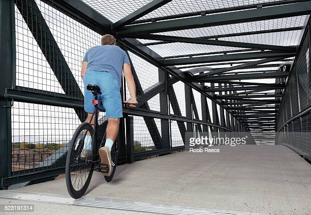 A young, adult man riding his bicycle on an urban bridge