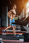 Young muscular adult man running on treadmill in gym. The athlete is in good shape. Personal trainer. Motion blur