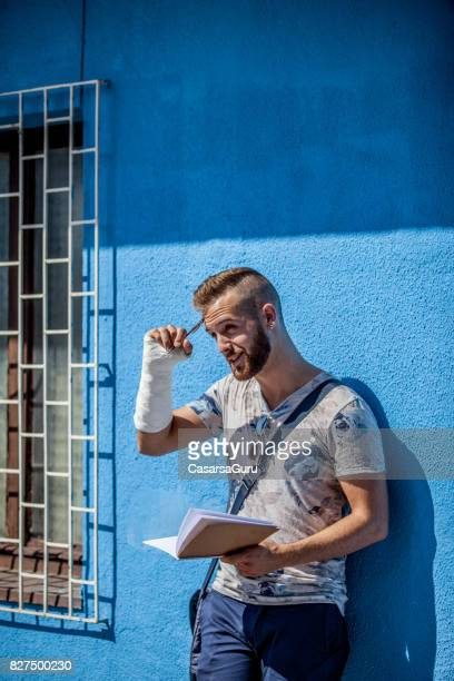 Young Adult Man Standing against Wall and Reading a Book