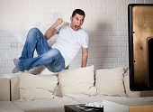 Young adult man watching football on television: Goal!