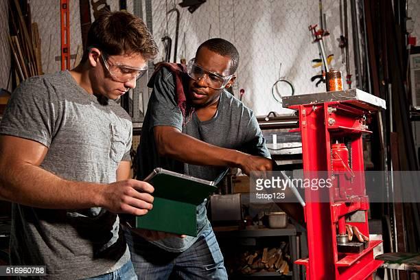 Junger Erwachsener Mechanik in kleinen business-Reparatur-workshop. Digitaltablett.