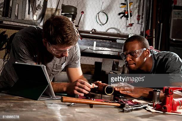 """Jeune adulte mécanique en réparation d'affaires en petit comité, l """" atelier. Tablette numérique."""