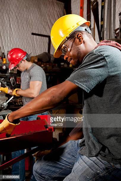 """Jeune adulte mécanique en réparation d'affaires en petit comité, l """" atelier. En pause."""