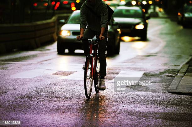 Jeune adulte à vélo dans la ville, quel que soir trafic
