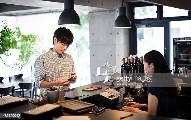 Young adult paying at a restaurant