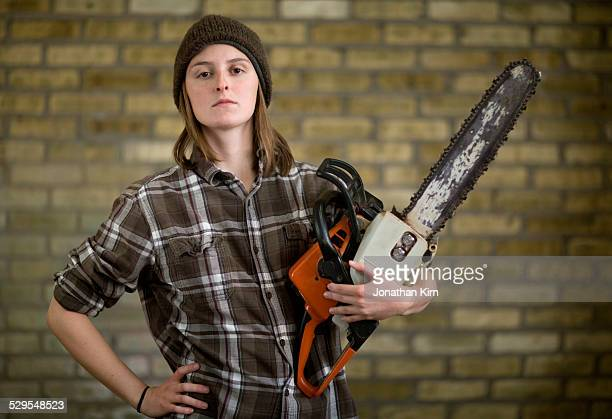 Young adult with a chainsaw portrait