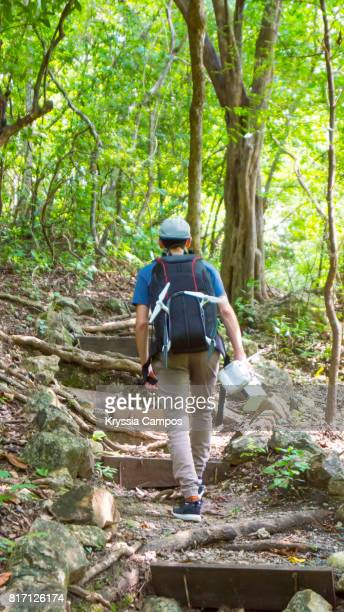 Young Adult with Backpack Trekking in Rainforest