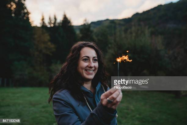 Young adult woman holding a sparkler firework
