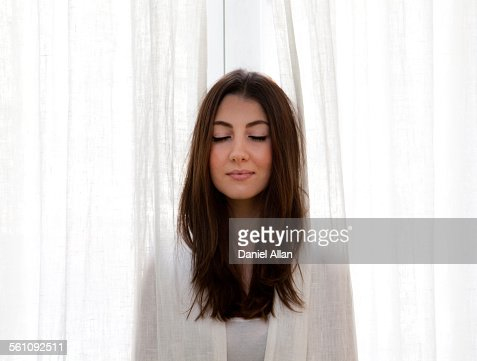 Young adult woman poking head out of curtains eyes closed for Curtains for young adults