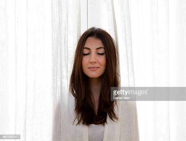 Young adult woman poking head out of curtains, eyes closed