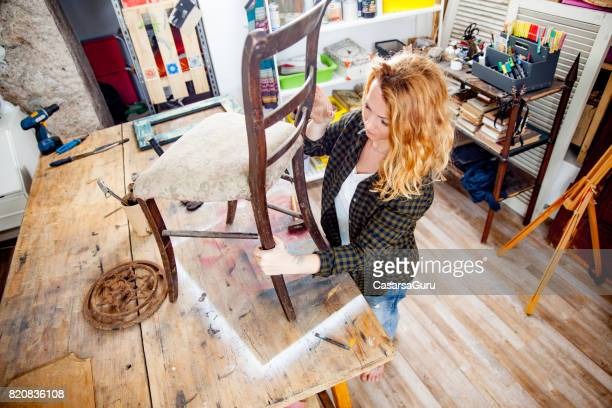 Young Adult Woman Restoring a Vintage Chair