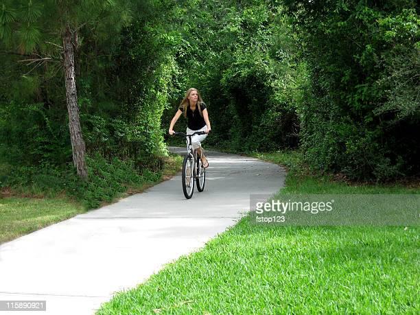 Adulto joven mujer montando Sendero para bicicletas, con mesas en la acera. Ejercicio. El verano. La naturaleza.