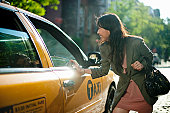 Young adult woman talking to taxi drive