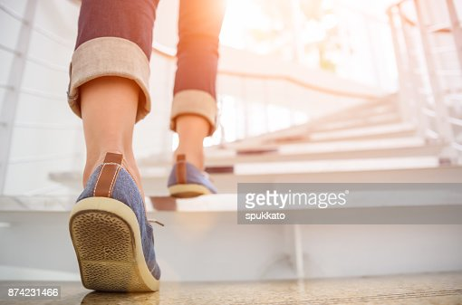 Young adult woman walking up the stairs with sun sport background. : Foto de stock