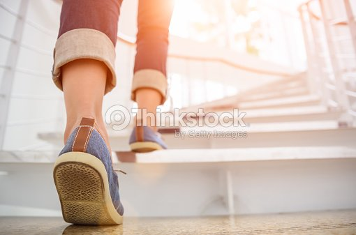 Young adult woman walking up the stairs with sun sport background. : Stock Photo