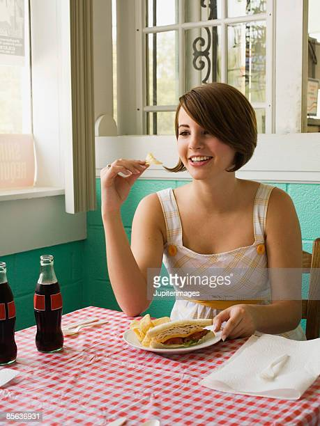 Young adult woman with sandwich and potato chips