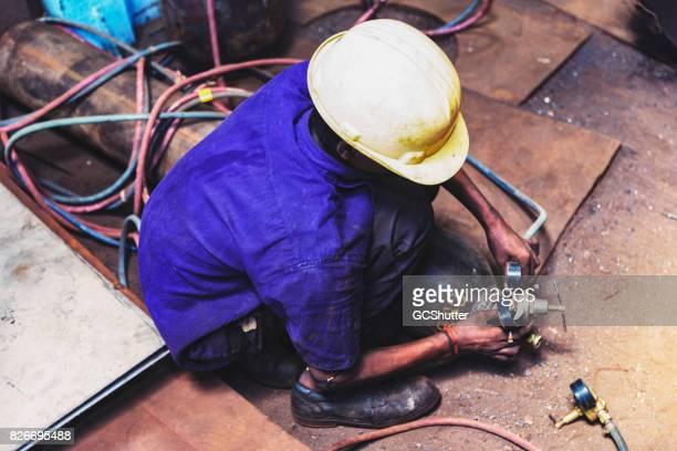 Jonge volwassen werken ter voorbereiding van de lucht druk gauge