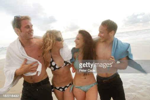 Young adults, arm in arm, on beach, by sea : Stock Photo