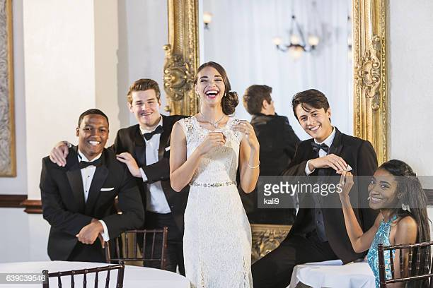 Young adults at party wearing tuxedos and gowns