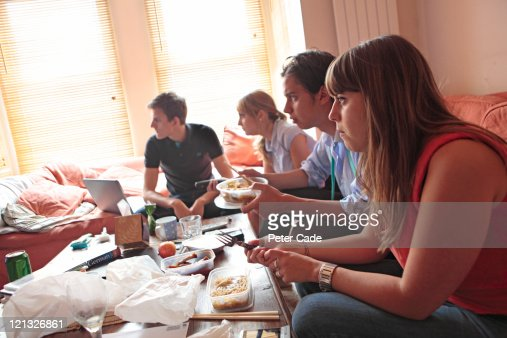 young adults eating dinner in shared house : Stock Photo