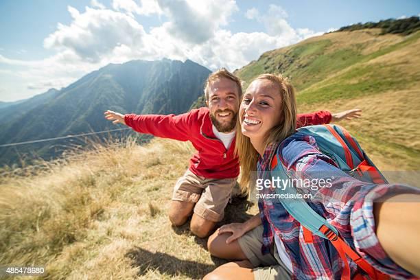 セルフィーを取る若い山のハイキングのトップ