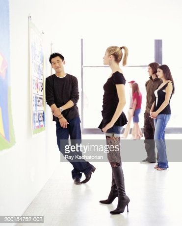 Young adults in art gallery, man leaning on wall : Stock Photo